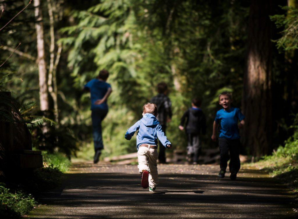 Child running on forest trail