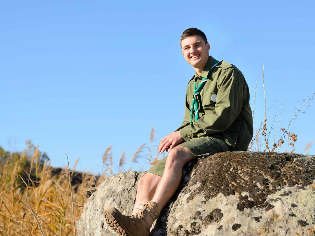 Eagle scout sitting on rock