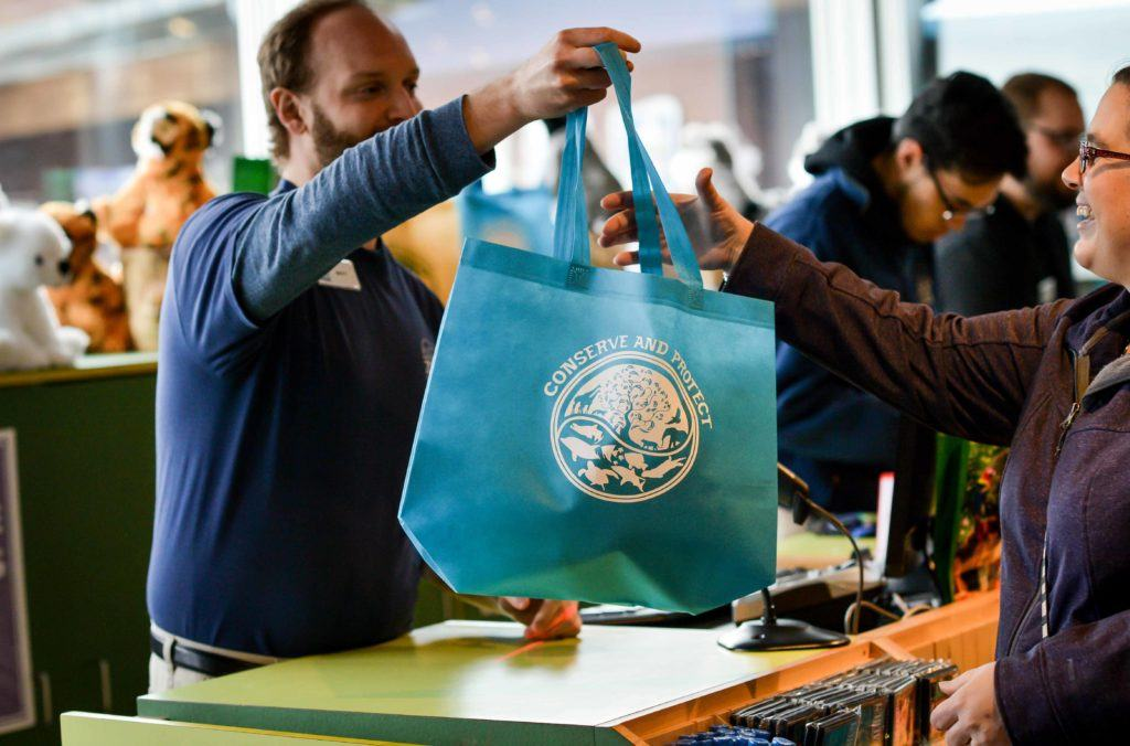 Staff holding reusable bag in gift shop.