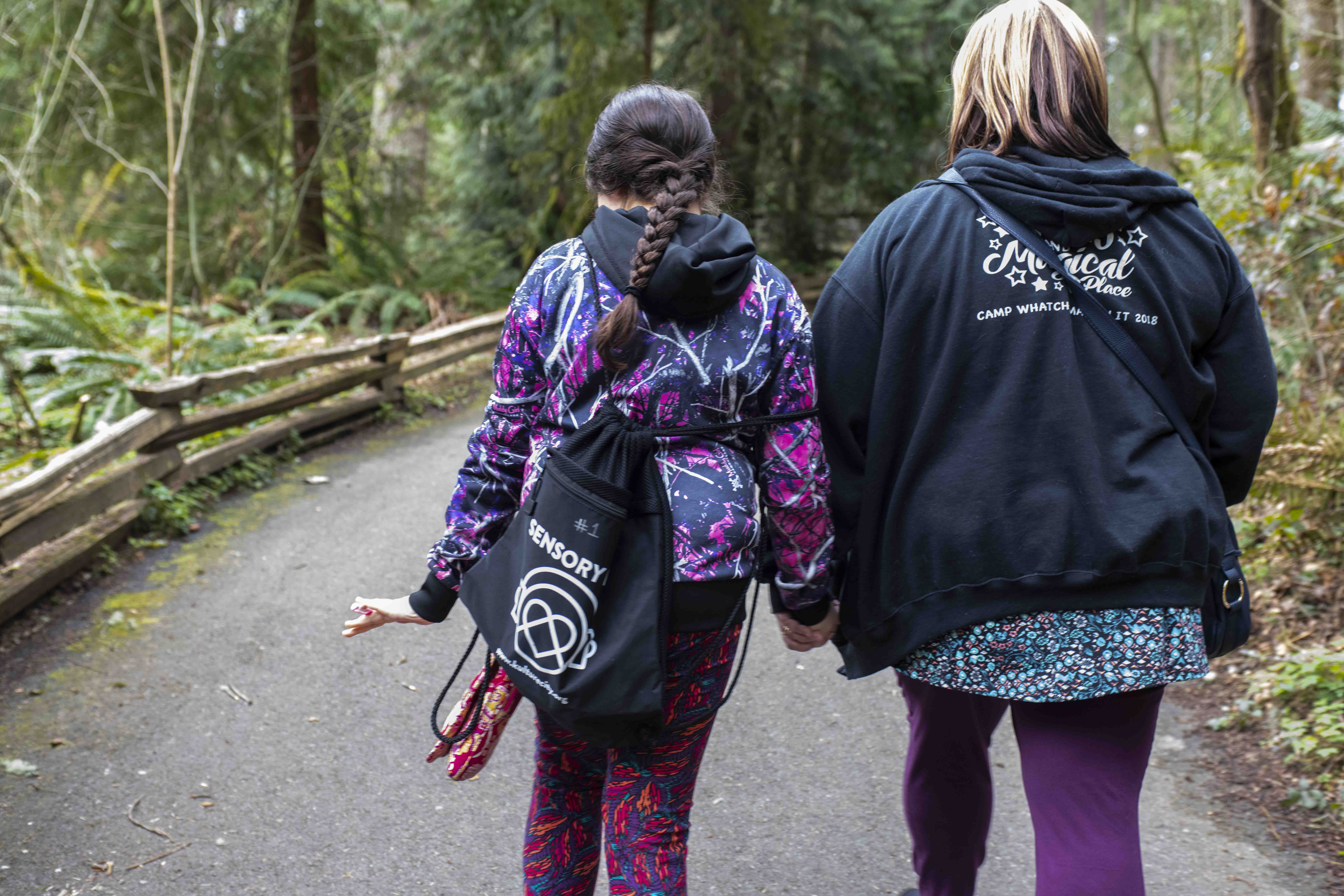 Mom and girl with sensory bag on trail