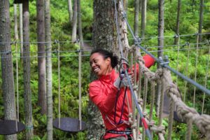 woman climbing ropes on zip line
