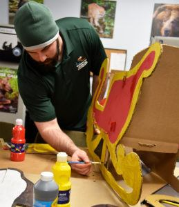 man paints cardboard sleigh