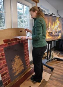 woman paints fireplace on cardboard