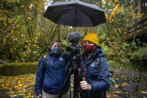 two women filming under umbrella in park